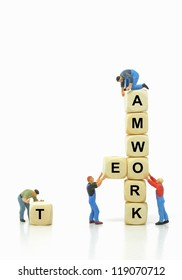 Mini workmen building together in teamwork concept with copy space