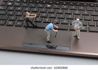 the Mini workmen repairing a laptop key board.