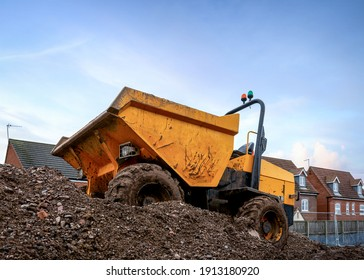Mini yellow dumper with roll bar and orange flashing lights and tipper front bucket  parked on construction mound of soil on new houses industrial building site