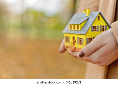 Mini yellow house model in woman hands. Mortgage offers, cozy home, homecare and clear concept