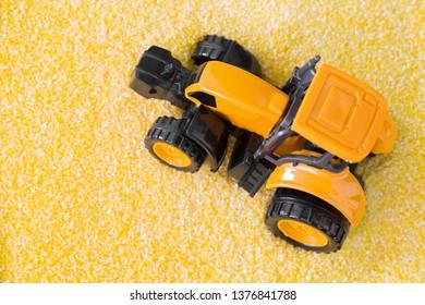 Mini yellow tractor driving on Polenta, yellow Cornmeal flour, Semolina grains, conceptual photo