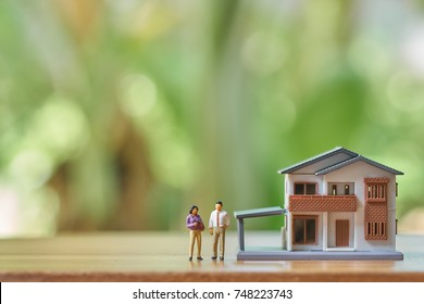 Miniature 2 people standing model house model.as background real estate concept with copy space.