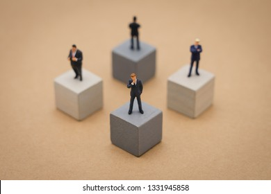 Miniature 4 people businessmen standing on Wooden cube Investment Analysis Or investment Blockchain concept. as background business concept and strategy concept with copy space.