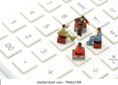 Miniature 4 people sitting on red staples placed on a white calculator. meeting or Discussion as background business concept with  copy spaces for your text or design.