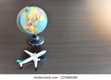 Miniature Airplane and Mini Globe Isolated on Wooden Table