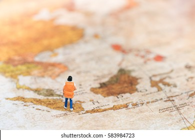 Miniature backpacker on vintage map using as background travel or business concept.