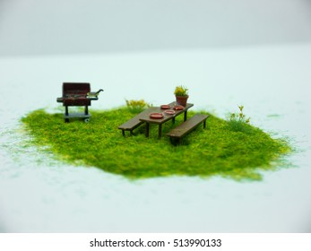 Miniature Barbecue with Wooden Table on grass with white background