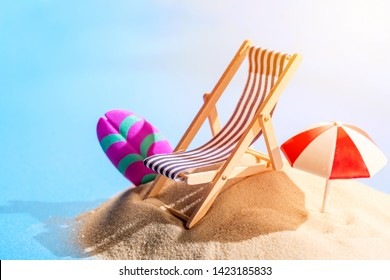 Miniature beach with deck chair, umbrella, parasol and surfboard on tropical islands sand surrounded by water. Tropical resort and vacation concept.