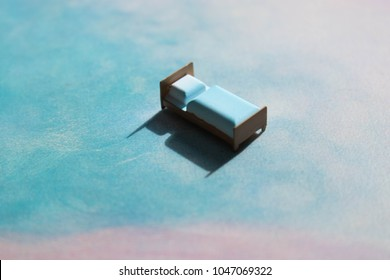Miniature bed floating on a cloudy pink and blue surreal landscape. Sleep, dream, or rest concept with heavy shadows and pastel colours.