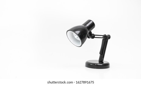 Miniature of black  color swing arm study desk lamp or studio light with led bulb. Concept of minimalist modern highlight. Isolated on empty background. Copy space.