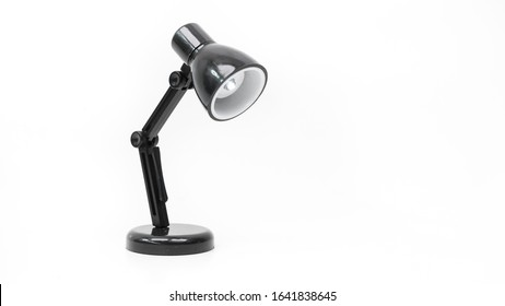 Miniature of black and white color swing arm study desk lamp or studio light with led bulb. Concept of minimalist modern highlight. Isolated on empty background. Copy space.