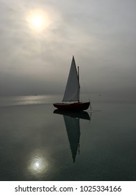 miniature boat floating on a small tub beside sea under the sun in the morning