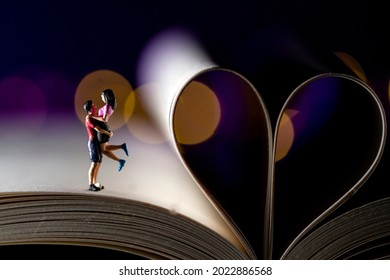 Miniature book lovers on a open book with bokeh hearts