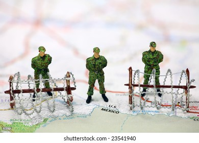 Miniature border patrol guards stand on a map at the USA/Mexico border with barbed wire. Border protection concept.