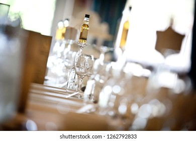 A miniature bottle of whiskey sat on an unturned wine glass