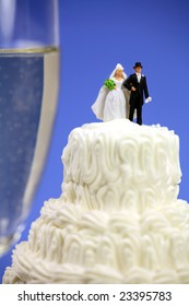 Miniature bride and groom on top of a wedding cake. There is a glass of champagne in the background. Marriage concept.