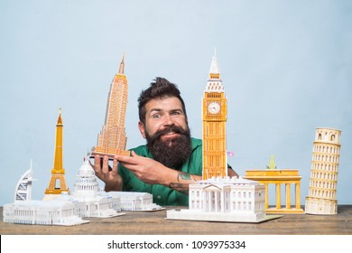 Miniature buildings illustrating travel. Travel concept - happy bearded man holds model Empire State Building. Miniature world architectural landmarks. Travel, vacation, holiday. Around world tours.