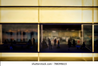 miniature business concept of Silhouette success businessman raise hand inside office building with blurred people model background.