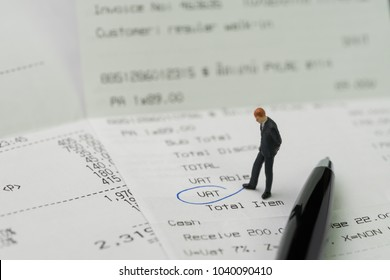 Miniature business man figurine standing on printed payment invoice, bill or receipt and looking at VAT with pen circle using as tax, accounting and business expenses concept.