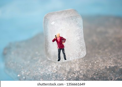 Miniature business man frozen in time talking on his outdated cell phone. Ice man trapped by modern technology. Boss or employee is left out in the cold. Problems working in tech. Man chilling out.