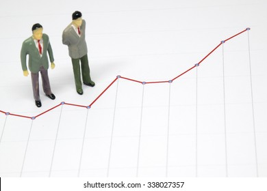Miniature business man looking at red line chart