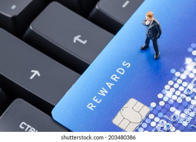 miniature business man on the keyboard with credit card, online shoping concept