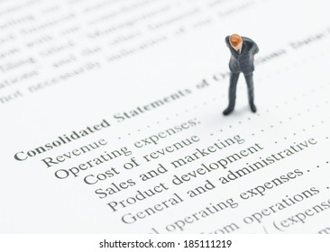 miniature business man stand on financial statement