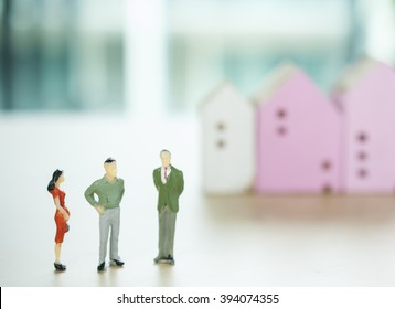 Miniature business people negotiating witth blur house mode background