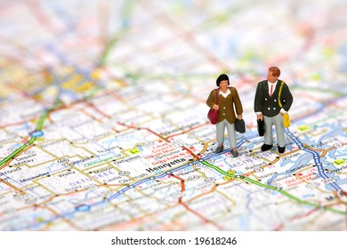 Miniature business travelers holding luggage and standing on a map.