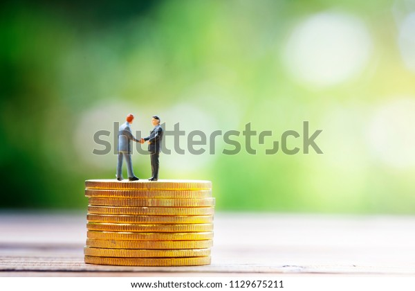 miniature businessman handshak on gold coin with nature green background