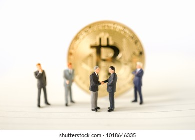 Miniature businessman handshake success deal business with Gold bitcoin background commitment, insurance agreement, travel investment and partnership bit coin business concept