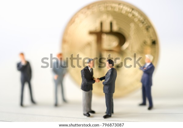 Miniature businessman handshake success deal business with Gold bitcoin background commitment, insurance agreement, travel investment and partnership bitcoins business concept