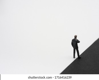 A miniature businessman having one foot in black background. The dark side concept image.