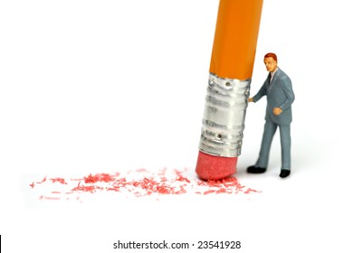 Miniature businessman holds a pencil and erases a mistake. Business, corporate, or accounting mistake concept.