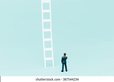 Miniature businessman and ladder