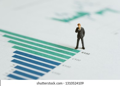 Miniature businessman leader standing with bar graph and chart of company annual report with vision of year 2019 revenue growth in green bar, forecast of company profit and stock investment concept.