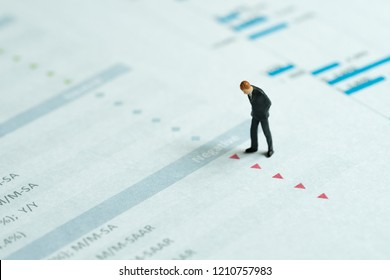 Miniature businessman looking at red down arrows of investment report, stock price drop, negative sentiment, financial crisis, situations in which some financial assets suddenly lose or value drop.