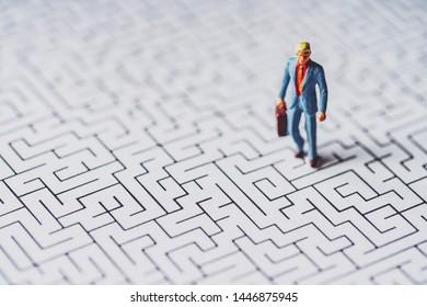 Miniature businessman lost in maze