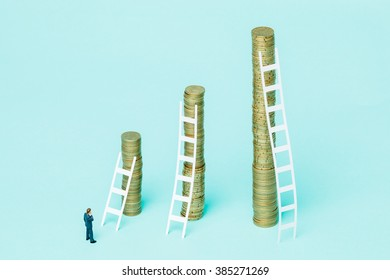 Miniature businessman observing three stacks of coins trying to choose the best investment.