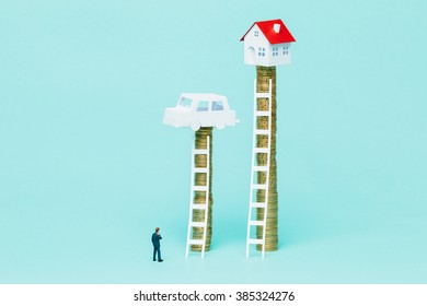 Miniature businessman observing two stacks of coins with a car and a house on top.