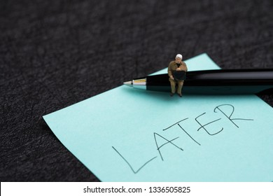 Miniature businessman sitting on pen and sticky note with hand writing the word Later on dark black background using as procrastination, lazy and postpone concept.