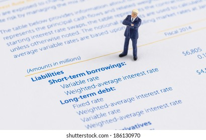 miniature businessman stand on the balance sheet