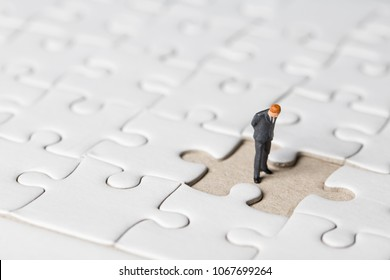 Miniature businessman stand on white jigsaw. One jigsaw are missing from board. Business vision concept.