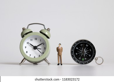 A miniature businessman standing between an alarm clock and a compass.