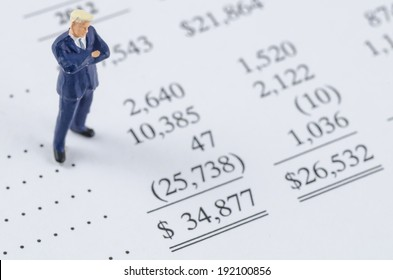 miniature businessman standing on the bottom line