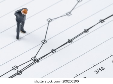 miniature businessman standing on the compare graph