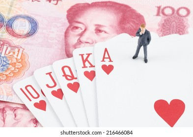 miniature businessman standing on the gamble card with Chinese yuan