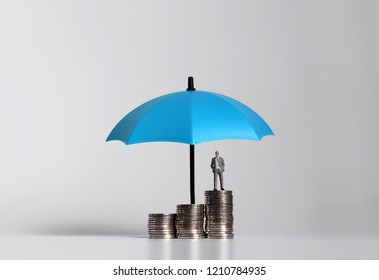 Miniature businessman standing on a pile of coins with umbrella.