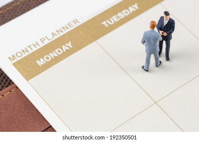 miniature businessman standing on the planner book