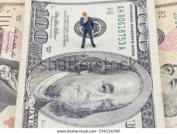 miniature businessman standing on the US dollar banknote